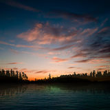 Abstract sunset background with forest lake and clouds Stock Photo