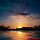 Abstract sunset background with forest lake and clouds Stock Images