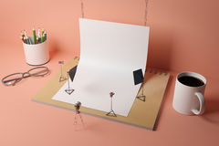 Abstract supplies photo studio. Abstract tiny photo studio made out of supplies: white paper, coffee cup, pencils, glasses and other items on peachy background Stock Image
