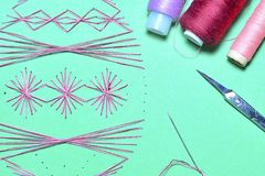 Abstract symmetrical patterns sewn on paper using cotton thread. Coils of thread, scissors and needle. royalty free stock photo