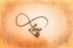 Abstract tattoo on skin that says love with smal red heart Stock Photography