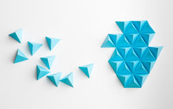 Abstract tetrahedron shape. Blue paper pyramids merging towards a shape, on white background Stock Image