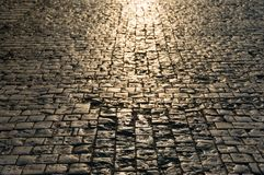 Abstract texture, background of sunlit road cobbles. Abstract texture, background of sunlit stone road cobbles royalty free stock photos
