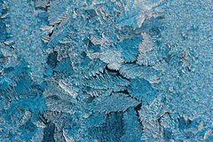 Abstract texture of blue ice patterns on glass close up Royalty Free Stock Photography