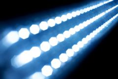 Abstract texture glowing lights on black background. blurred light strip. blue glow. many small glowing light bulbs. Halogen diodes bright substrate wallpaper Stock Photography