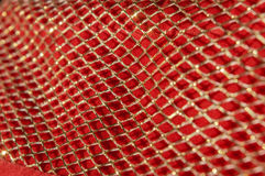 Abstract texture with gold shiny shimmering grid in the sun. Bright red Christmas background with golden elements. stock photos