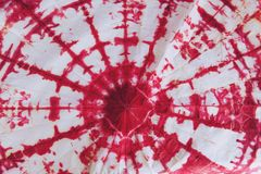 Abstract tie dyed fabric of red color on white cotton stock photos
