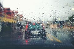 Road view through car window with rain drops. Abstract traffic in raining day. View from car seat. Background in retro filter. Road view through car window with royalty free stock photos