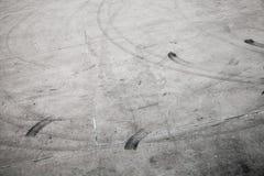 Dark tire tracks on gray concrete road stock image