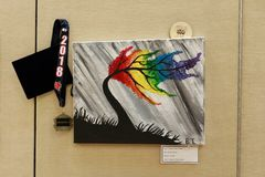 Abstract tree shown at art fair. An attractive tree bent by a storm but with its foliage painted in rainbow colors and exhibited at a local school district Art stock photos