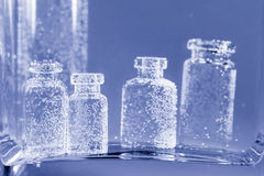 Abstract, underwater composition with small glass bottles Stock Photos