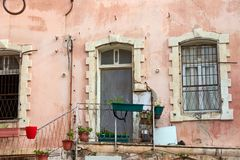 Abstract urban grunge background pink wall of house with arched openings of windows and doors with white window sills and red plan. Abstract urban grunge Royalty Free Stock Images