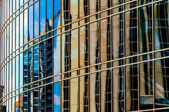 Abstract Urban Reflections with a Modern Sci-Fi Feel. This unidentified building has distorted reflections of other buildings and construction cranes Stock Photography