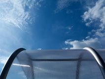 Abstract view of curved, domed glass storage hood. With aluminum frame and blue sky above with white clouds Royalty Free Stock Photo