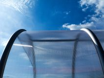 Abstract view of curved, domed glass storage hood. With aluminum frame and blue sky above with white clouds Stock Photography