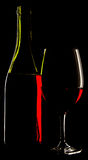 Abstract view of a glass wine and the wine bottle against a soli Royalty Free Stock Photos
