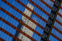 Abstract view of modern highrise glass building. Under construction, with reflection in window, at an angle royalty free stock photography