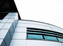 Abstract view of a modern, IT related headquarters showing its artistic presence. Details of the metal clade design, symmetry and curves are apparent in this Stock Image