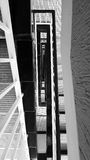 Abstract view of a stair case in black and white. Abstract view of a stairwell with black banisters and tiled floors Royalty Free Stock Image