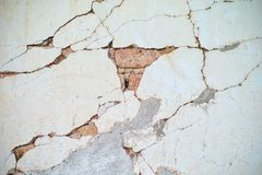 Abstract vintage texture and background of crack and broken plastered cement surface on the brickwork wall. At the construction site royalty free stock image