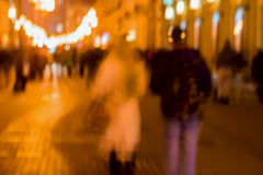 Abstract vintage tone motion. Blur image of Street, girl and guy walking along sidewalk, bright city lights with bokeh. Abstract vintage tone motion. Blurred Royalty Free Stock Image