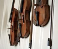 Abstract Violins. Close-up of three violins hanging on a wall Royalty Free Stock Images