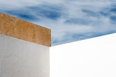 Abstract Wall and Sky. Abstract Angular White Wall with White Clouds and Blue Sky Royalty Free Stock Image