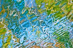 Beautiful abstract water reflection in blue, yellow and green colors. stock photography