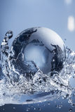 Abstract water splash. Glass globe planet in drop water splash on blue background Royalty Free Stock Photography