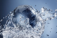 Abstract water splash. Glass globe planet in drop water splash on blue background Stock Image