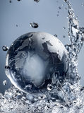 Abstract water splash. Glass globe planet in drop water splash on blue background Stock Photography