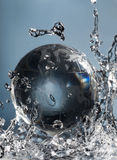 Abstract water splash. Glass globe planet in drop water splash on blue background Royalty Free Stock Photo
