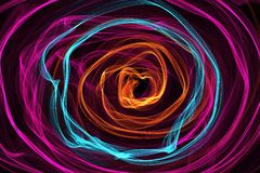 Abstract wave motion glowing lines on dark background. Circle Waves of glowing lines in different shapes and colors Stock Photo