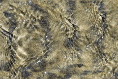 Abstract Wet Sand Patterns. Closeup of sea water rippling over sand on a beach stock image