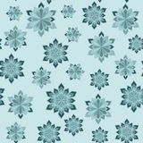 Abstract winter seamless pattern. Snowflakes of different sizes on a light blue background. Royalty Free Stock Photography