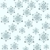 Abstract winter seamless pattern. Snowflakes of different sizes. On a light blue background. For your design Stock Images