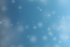 Abstract winter snow bokeh in blue sky blur background. Royalty Free Stock Images