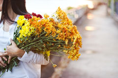 Abstract woman with bouquet flowers vibrant in hands on blur street Stock Photo
