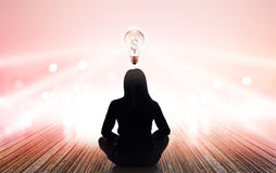 Abstract woman are meditating at rays of light pastel and light blub sign money on vibrant background Stock Image