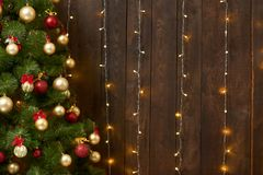 Abstract wooden background with christmas tree and lights, classic dark interior backdrop, copy space for text, winter holiday con. Cept royalty free stock images