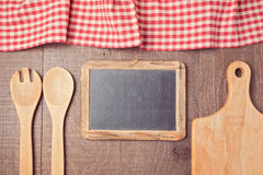 Abstract wooden background with red checked tablecloth, chalkboard and kitchen utensils. View from above Stock Photo
