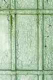 Abstract wooden wooden door background with cracks on green plaster paint. Royalty Free Stock Images