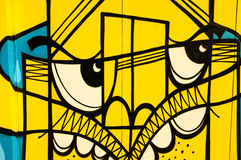 Abstract yellow graffiti face. Graffiti face painted in yellow and blue colours, Brick Lane, London Stock Photo