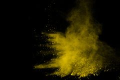 Abstract of yellow powder explosion on black background. Yellow powder splatted isolate. Colored cloud. Colored dust explode. Pain. T Holi royalty free stock photos
