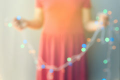 Abstract young girl holding out of focus Christmas lights decorations. Blurred background Stock Photos