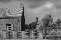 Abstract Zwart-wit beeld van oud die baksteenhuis met houten omheining bij platteland wordt omringd Royalty-vrije Stock Foto