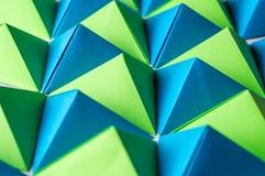 Abstracte achtergrond met blauwe, groene en gele origamitetrageders stock foto