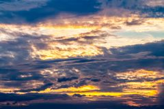 Abstracte achtergrond van kleurrijke dramatische hemel in schemering, met onweerswolken, het gouden, grijze en oranje, en zonlich stock afbeelding