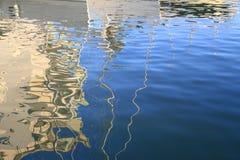 Abstracte bezinningen van boten en gebouwen in blauw gegolft water Stock Foto