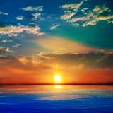 Abstracte blauwe aardachtergrond met overzees unset en wolken